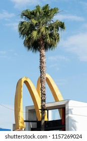 Los Angeles, CA, USA - May 26, 2018: McDonald's M sign behind a palm tree in Los Angeles.