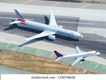 Los Angeles, CA / USA - May 30 2016: Air to air with Delta Airlines Connect Embraer 175 take off and American Airlines Boeing 777 at Los Angeles International Airport LAX. Aviation in United States.