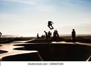 Los Angeles, California - 07 20 2019: Skateboarder jump at venice beach skate park at sunset