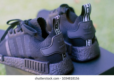 LOS ANGELES, CALIFORNIA - AUGUST 9, 2017: Adidas NMD R1 Primeknit Japan Triple Black shoes backside on black box with green blurred background.