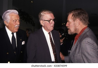 LOS ANGELES, CALIFORNIA - Exact date unknown - circa 1990 - Legendary actors Charlton Heston, Jimmy Stewart and Cesar Romero chatting at a celebrity event
