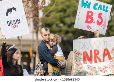 LOS ANGELES, CALIFORNIA - FEBRUARY 19, 2018: A father holds his young child at the People's Rally Against Gun Violence in Pershing Square.
