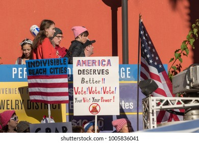 """LOS ANGELES, CALIFORNIA - JANUARY 20, 2018:  2nd Annual Women's March marcher  with a sign that reads, """"America deserves better!! Vote! Vote! Vote! Your Vote! Your Power!"""""""