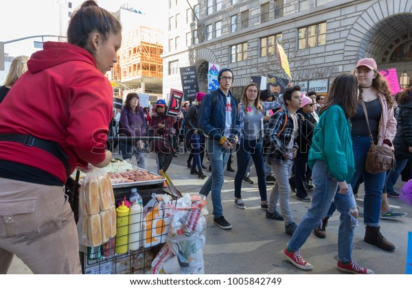 LOS ANGELES, CALIFORNIA - JANUARY 20, 2018:  2nd Annual Women's March marchers passing by a street food vendor along the march route.
