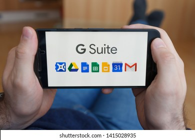 LOS ANGELES, CALIFORNIA - JUNE 3, 2019: Close up to male hands holding smartphone using G Suite application. An illustrative editorial image