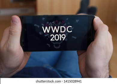 LOS ANGELES, CALIFORNIA - JUNE 3, 2019: Close up to male hands holding smartphone watching WWDC 2019. An illustrative editorial image