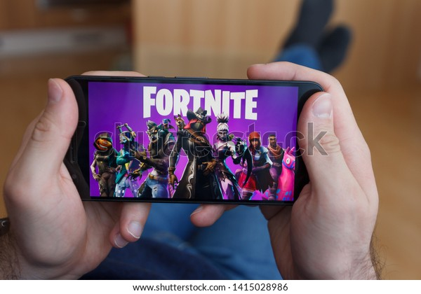 LOS ANGELES, CALIFORNIA - JUNE 3, 2019: Lying Man holding a smartphone and playing the Fortnite game on the smartphone screen. An illustrative editorial image.