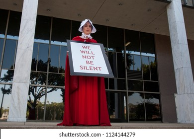 Los Angeles, California - June 30, 2018: A woman dressed as a handmaid from the novel and television series A Handmaid's Tale to protest the Trump Administration at the Families Together March Rally.