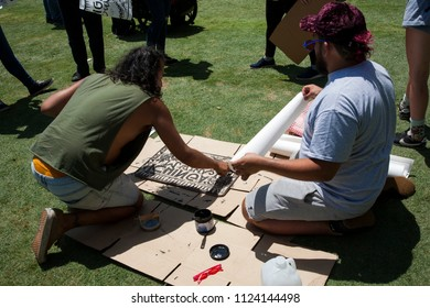 Los Angeles, California - June 30, 2018: Two men create protest signs at the Families Together March and Rally in Grand Park, Downtown Los Angeles to protest immigrant families being separated.