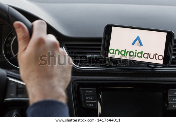 LOS ANGELES, CALIFORNIA - JUNE 6, 2019: Close up to male driving and using navigation appliction Google Android Auto. An illustrative editorial image