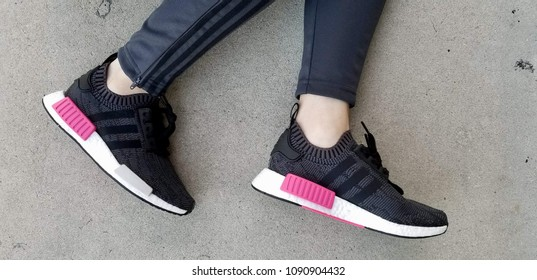 LOS ANGELES, CALIFORNIA - MAY 3, 2018: TOP VIEW ADIDAS NMD R1 PK BLACK AND PINK SHOES WITH LEGS ON CONCRETE SURFACE.