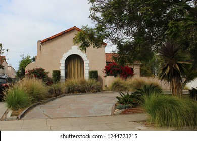 LOS ANGELES, CALIFORNIA - NOVEMBER 08, 2018: Brown home outside in LA area with white detailing around the window and lots of green plants outside including a huge tree and a black car parked outside.