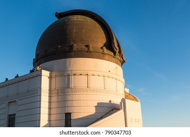 LOS ANGELES, CALIFORNIA - NOVEMBER 19, 2017:  People view the Hollywood hills at sunset from atop Griffith Observatory, near the dome housing a Zeiss 12-inch refracting telescope.