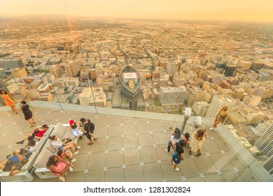 Los Angeles, California, United States - August 9, 2018: aerial view of tourists take photo onpanoramic terrace at twilight. People look at LA Downtown skyline from Oue Skyspace U.S. Bank Tower.