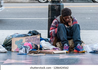 Los Angeles, California, United States of America - January 8, 2017. Homeless man on Sunset Boulevard in Los Angeles, sitting on the ground with his belongings and looking into smartphone.