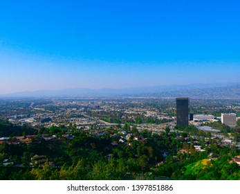 Los Angeles, California, United States – May 1, 2019: Universal City overlook.  Comcast NBC Universal office building. Rooftop name on the building at shiny summer day. Mountains view.