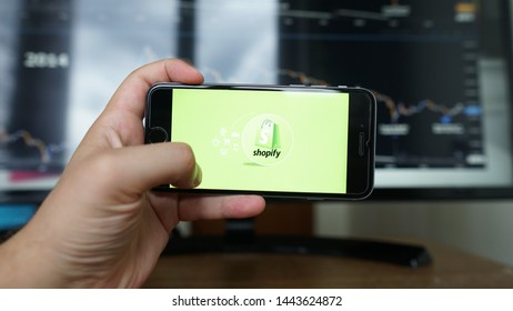 Los Angeles, California, USA - 06 July 2019: A Man holds  iPhone with Shopify application on the screen in coffee shop. Shopify is an e-commerce platform for online stores