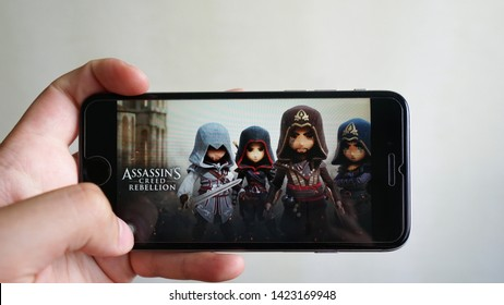 Los Angeles, California, USA - 13 June 2019: Hands holding a smartphone with  Assassin's Creed Rebellion game on display screen