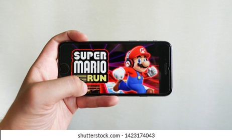Los Angeles, California, USA - 13 June 2019: Hands holding a smartphone with  Super Mario Run mobile game on display screen