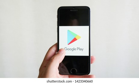 Los Angeles, California, USA - 13 June 2019.Young man holding smartphone with Google play store logo with the finger on the screen