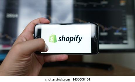 Los Angeles, California, USA - 14 July 2019: A Man holds  iPhone with Shopify application on the screen in coffee shop. Shopify is an e-commerce platform for online stores