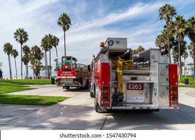 Los Angeles, California / USA - 16 Oct 2019: Venice Beach, two red fire trucks T63 / E263 park between green palms. Wispy clouds sweep diagonally across blue sky forming an RGB additive colour scene.