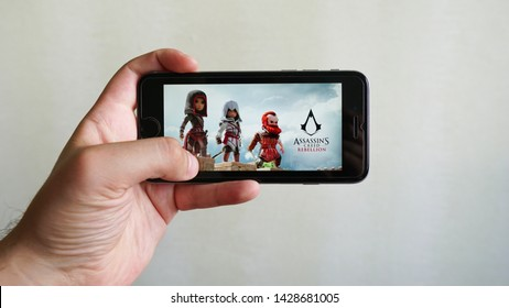 Los Angeles, California, USA - 19 June 2019: Hands holding a smartphone with  Assassin's Creed Rebellion game on display screen