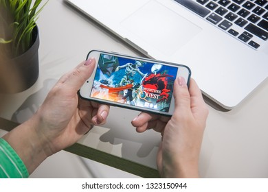 Los Angeles, California, USA - 25 February 2019: Hands holding a smartphone with Adventure Quest game on display screen
