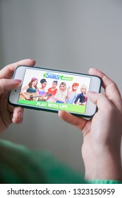 Los Angeles, California, USA - 25 February 2019: Hands holding a smartphone with Sims Mobile game on display screen, Illustrative Editorial