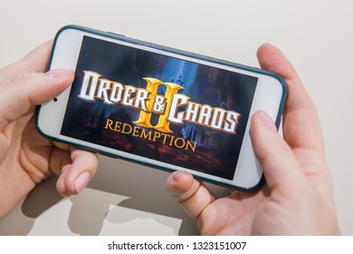 Los Angeles, California, USA - 25 February 2019: Hands holding a smartphone with Order and Chaos 2 game on display screen, Illustrative Editorial
