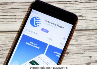 Los Angeles, California, USA - 25 January 2020: Logo of WebMoney Keeper mobile app on phone screen close up top view on wooden table, Illustrative Editorial.