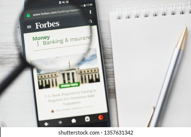 Los Angeles, California, USA - 3 April 2019: Forbes, American business magazine official website homepage under magnifying glass. Concept Business magazine logo visible on smartphone, tablet screen