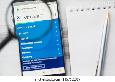 Los Angeles, California, USA - 3 April 2019: VMware Computer software official website homepage under magnifying glass. Concept VMware Computer software logo visible on smartphone, tablet screen
