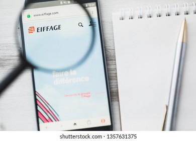 Los Angeles, California, USA - 3 April 2019: Eiffage S.A. official website homepage under magnifying glass. Concept Eiffage Civil engineering, construction logo visible on smartphone, tablet screen