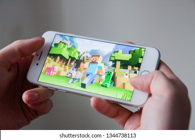 Los Angeles, California, USA - 8 March 2019: Hands holding a smartphone with Minecraft Pocket Edition game on display screen, Illustrative Editorial