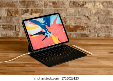 Los Angeles, California / USA - April 29, 2020: Apple iPad attached to the Magic Keyboard and charging with a white USB-C cord/cable on a wooden desk with an Apple Pencil on the side