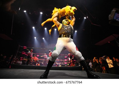 Los Angeles, California, USA; April 5, 2012; Mexican wrestlers, or luchadores, compete during the 'Lucha VaVoom Cinco de Mayan' at The Mayan Theatre. Lil Chicken is held overhead by his competitor.