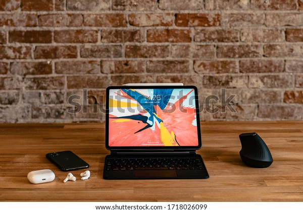 Los Angeles, California / USA - April 29, 2020: Work from home setup with an iPad, Magic Keyboard, mouse, iPhone 11 Pro and Air Pods