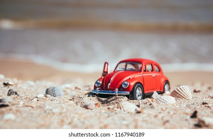 Los Angeles, California / USA - August 11 2018: A 1:18 scale model of a beautiful red  Volkswagen Beetle made by Auto Art on the background of a sandy sunny beach in Los Angeles, California, USA