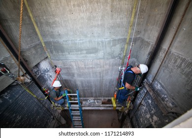 Los Angeles, California / USA - August 2, 2018: Elevator technicians are installing an elevator rails into the old shaft as part of new downtown old building renovation.