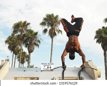 LOS ANGELES, CALIFORNIA, USA - AUGUST 25, 2015: a bodybuilder performs a handstand at muscle beach in venice, ca