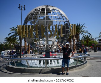"""Los Angeles, California, USA - August 30, 2016: Tourist Man pointing at """"Universal Studios Globe"""" with Blue Sky Background in Universal Studios at Los Angeles, California."""