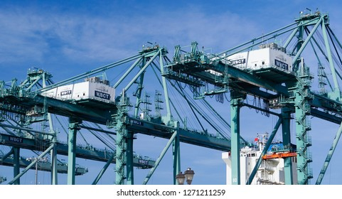 Los Angeles, California USA - December 30, 2018: Tall gantry cranes in a modern industrial shipping harbor operation with the bridge of a container ship visible, used for loading and unloading import