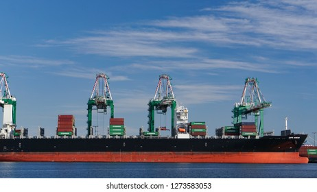 Los Angeles, California USA - December 30, 2018: Container ship Cape Akritas being loaded by gantry cranes at a freight terminal in the Port of Los Angeles