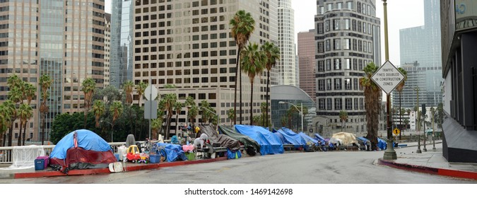 Los Angeles, California, USA - December 6, 2018: Panoramic shot of homeless tents lining offramp to freeway, downtown Los Angeles. Nice buildings in background.