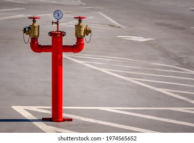 """Los Angeles, California USA - Feb 6, 2020: Tall, bright red parking lot standpipe with three """"arms"""" sits alone in a parking lot.  There is a pressure gauge in the center along with two brass valves"""