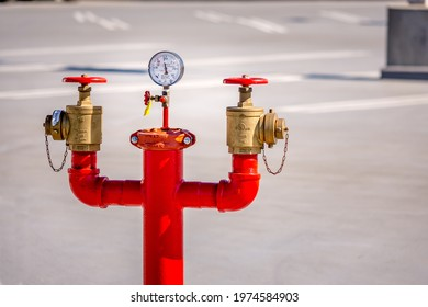 Los Angeles, California USA - Feb 6, 2020: Close up view of a tall, red standpipe in an empty parking lot.  There is a pressure gauge in the center along with two brass valves on both sides.