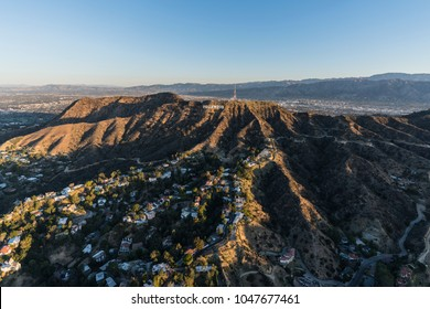 Los Angeles, California, USA - February 20, 2018:  Morning aerial view of canyon homes and Hollywood Sign in Griffith Park with the San Fernando Valley in background.