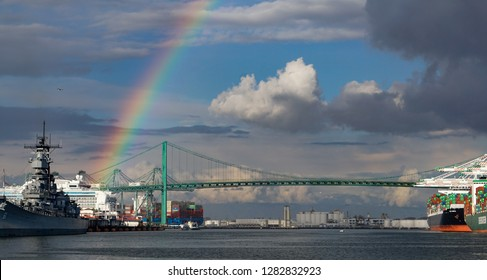 Los Angeles, California USA - January 12, 2019: A rainbow over the Port of Los Angeles main channel, Battleship Iowa, a cruise ship, container port operations and Vincent Thomas suspension bridge