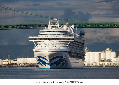 Los Angeles, California USA - January 12, 2019: Ruby Princess cruise ship on an outbound voyage from Port of Los Angeles in front of Vincent Thomas suspension bridge, cargo terminals, mountains